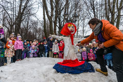 Maslenitsa (pancake week). Man sets fire to an effigy of Winter, around which there are people. Royalty Free Stock Images