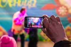 Maslenitsa (pannekoekweek) Mensenspruiten op de telefoon, aangezien de trainer met de beer op stadium presteert Stock Afbeeldingen