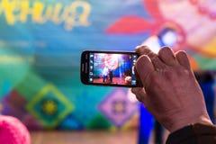Maslenitsa (pannekoekweek) Mensenspruiten op de telefoon, aangezien de trainer met de beer op stadium presteert Royalty-vrije Stock Afbeeldingen