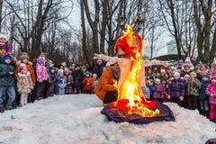 Maslenitsa (semana da panqueca) O homem ajusta o fogo a uma efígie do inverno, em torno de que há povos Imagem de Stock Royalty Free
