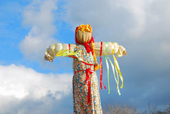 Maslenitsa doll. Blue sky with clouds background. Stock Images