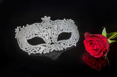 Mask with rose. Masquerade mask on a black background with red rose. Image reflected on black Royalty Free Stock Photography