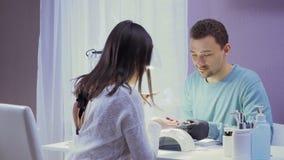 Masnicure domina pontas do tratamento de mãos das mostras do homem ao cliente filme