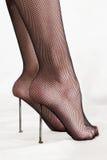 Masochistic foot fetish. Closeup of woman wearing black stockings balancing heels on sharp nails, isolated on white background Stock Photo