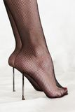 Masochistic foot fetish. Closeup of two long nails under heels of masochistic woman wearing stockings, isolated on white background. Masochistic foot fetish Stock Photo