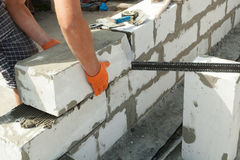 Mason aligning aerated autoclaved concrete block of constructed house wall. Royalty Free Stock Photography