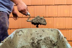 Mason with brick house on construction site. Construction worker with trowel on walls of a shell in solid construction. representative photo of the black economy Royalty Free Stock Photo