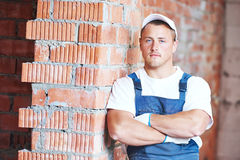 Mason bricklayer standing near brickwall Stock Images