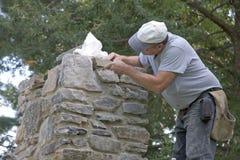 Mason Building Chimney. Mason Building a Stone Chimney stock image