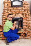 Mason building masonry heater. Fitting the thermal glass into the door Royalty Free Stock Photos