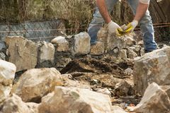 Mason building a stone wall, authentic working person royalty free stock image