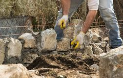 Mason building a stone wall, authentic working person royalty free stock photo