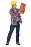 Mason carrying a cinderblock Royalty Free Stock Image