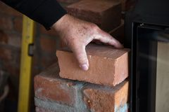 Mason checks a brick for a wall at the edge of the fireplace royalty free stock photo