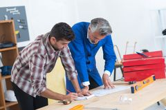 Mason and engineer measuring plans royalty free stock images