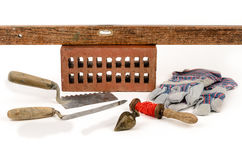 Mason equipment. Old construction accessories trowel, bricks, plummet and level on white background Stock Image