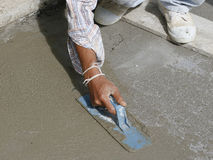 Mason hand finishes a newly poured concrete floor royalty free stock image