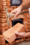 Mason hands with brick and hammer Stock Photo