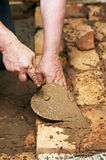 Mason hands at bricklaying works Stock Photos