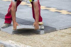 Mason hands laying paver bricks Royalty Free Stock Images