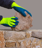 Mason hands working on masonry stone wall Stock Image