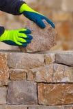 Mason hands working on masonry stone wall Royalty Free Stock Photos