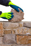 Mason hands working on masonry stone wall Stock Photo