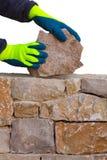 Mason hands working on masonry stone wall Stock Photo