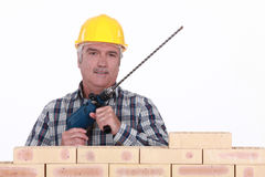 Mason holding brick drill Stock Photos