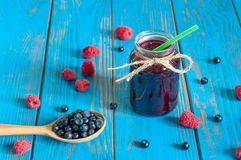 Mason jar with berries jam or marmalade and fresh. Raspberry, blueberry on a rustic wooden table. Cooking background Stock Image