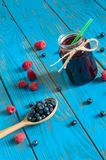Mason jar with berries jam or marmalade and fresh. Raspberry, blueberry on a rustic wooden table. Cooking background, unique perspective Stock Image