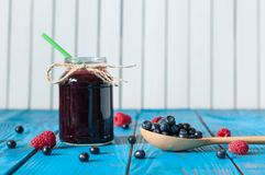 Mason jar with berry jam or marmalade and fresh. Raspberry on a rustic wooden table. Cooking background Stock Photos
