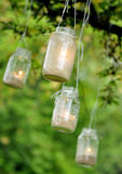 Mason jar candles hanging from a tree Royalty Free Stock Photography
