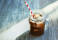 Mason jar with cold brew coffee and straw. On wooden table stock images