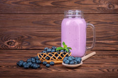 A mason jar filled with fresh blueberry smoothie on a wooden background. A heap of bright ripe berries near a full can of berry yo. A close-up of a large mason Stock Photos