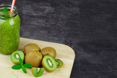 A mason jar filled with kiwi beverage, leaves of mint on a light wooden board on a dark stone background. Copy space. stock photo