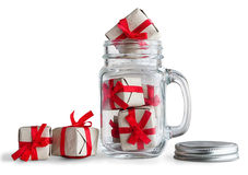 Mason jar filled with small gift boxes. Royalty Free Stock Images