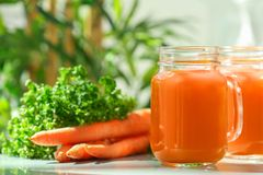 Mason jar of fresh carrot juice. On table stock photography