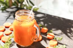 Mason jar of fresh carrot juice. On table stock photos