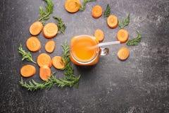 Mason jar of fresh carrot juice with slices. On grunge background Royalty Free Stock Photos