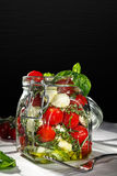 Mason jar with fresh mixed vegetables. On dark background Stock Images