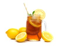 Mason jar glass of iced tea with lemons isolated on white. Mason jar glass of iced tea with lemons and straw isolated on a white background Stock Photography