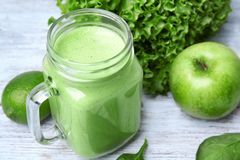 Mason jar of green healthy juice with ingredients. On wooden table Stock Photo