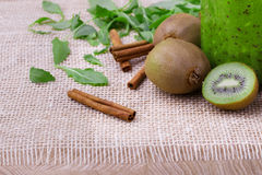 A mason jar of green smoothie from kiwi, cinnamon sticks and leaves on a white tablecloth. Kiwi fruits for beverages. Royalty Free Stock Image