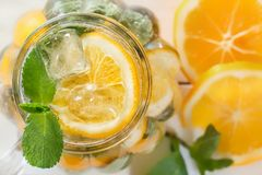 Mason jar of a homemade lemonade with mint and ice, citrus slices on a rustic white wooden background royalty free stock images