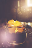 Mason jar with jelly candies in sunset. Mason jar full of jelly candies in sunset illuminated kitchen with bokeh light effect. Selective focus, image toned Stock Photo