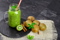 A mason jar of kiwi smoothie. Kiwis with cinnamon and mint on a dark background. Natural summer breakfast. Copy space. A composition of tropical kiwis, mason royalty free stock image