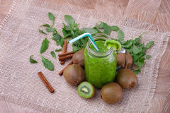 A mason jar of kiwi smoothie with straw, cinnamon sticks and leaves on a wooden background. Kiwi fruits for desserts. Stock Photography
