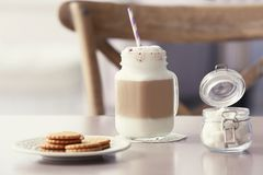 Mason jar with latte macchiato. On table indoors Royalty Free Stock Photography