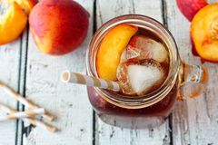 Mason jar of peach iced tea on wood, downward view. Mason jar glass of homemade peach iced tea on a rustic white wood background, downward view stock photography